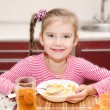 Cute smiling little girl having breakfast cereals with milk — Stock Photo #68552091