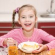 Cute smiling little girl having breakfast cereals with milk — Stock Photo #68552347