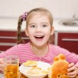 Cute smiling little girl having breakfast cereals with milk — Stock Photo #68552349