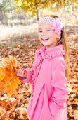 Autumn portrait of adorable little girl with maple leaves — Stock Photo