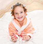 Happy funny little girl with manicure and hair curlers — Stock Photo