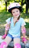 Mignonne petite fille souriante en patins à roulettes rose — Photo
