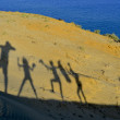 Silhouettes of cheerful happy family enjoying hiking a beautiful islands sand dunes — Stock Photo #69231559