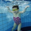 Funny happy toddler girl swimming underwater in a pool with lots of air bubbles — Stock Photo #69239015