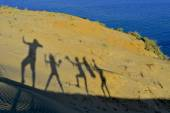 Silhouettes of cheerful happy family enjoying hiking a beautiful islands sand dunes — Stock Photo