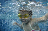 Funny happy toddler girl swimming underwater in a pool with lots of air bubbles — Stock Photo