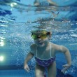 Funny happy toddler girl swimming underwater in a pool with lots of air bubbles — Stock Photo #69240455