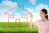 Business woman drawing house on the meadow — Stock Photo