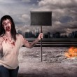 Female zombie holding wooden board over city on fire — Stock Photo #82824804