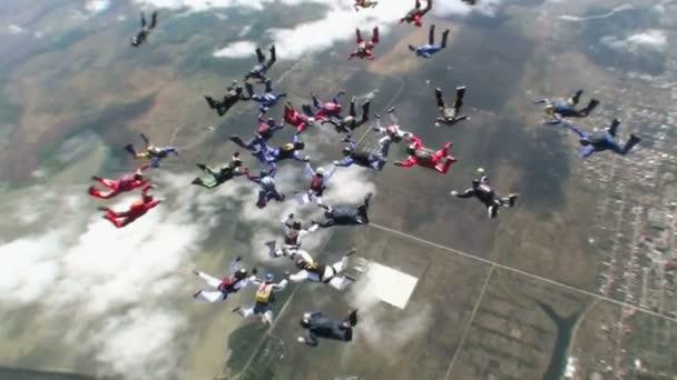 Paracaidistas en el cielo sobre la ciudad — Vídeo de stock
