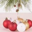 Pine tree branch with red, white and gold Christmas baubles close-up — Stock Photo #58346241