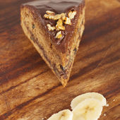 Piece of chocolate with banana and nuts cake on wood background — Stock Photo