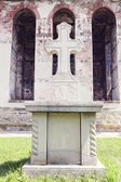 Close image of stone cross in front of painted church wall in Moldovita Monastery — Stock Photo