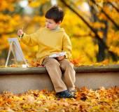 Lindo niño pintando en el parque otoño dorado — Foto de Stock