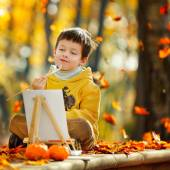 Cute little boy painting in golden autumn park — 图库照片