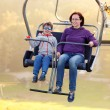 Happy mother and son ride chair lift — Stock Photo #55279855