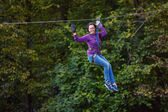 Young woman having fun on long rope route — Stock Photo