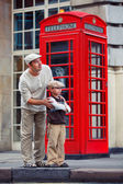 Father and son outdoors by red phone booth — Stock Photo