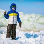 Cute little boy outdoors standing on winter beach — Stock Photo #65630589