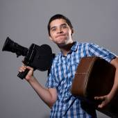 Portrait of a young cameraman with old movie camera and a suitca — Foto Stock