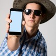 Young man wearing sunglasses and a hat in his hand phone shows — Stock Photo #53090139