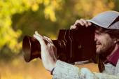 A man wearing a cap with an old movie camera.  — Stock Photo