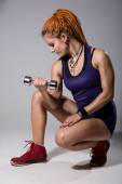 A young girl with dreadlocks training with dumbbells. — Stock Photo