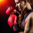 Beautiful girl with red boxing gloves, dreadlocks on a black bac — Stock Photo #56197095