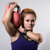 Portrait close up of young attractive female doing kettle bell e — Fotografia Stock