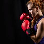 Beautiful girl with red boxing gloves, dreadlocks on a black bac — Stock Photo