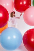 Beautiful girl in a white blouse is considering large balloons. — Stockfoto