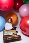 Girl schoolgirl with wooden abacus and lying in a suitcase with  — Stockfoto