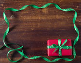 Red gift box with green ribbon lying on the wooden background — Stock fotografie