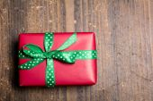 Red gift box with green ribbon with polka dots on a wood backgro — Stock fotografie