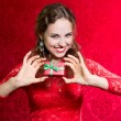 Happy young woman with a small gift in a red dress. — Stock Photo #58990253