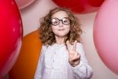 Young girl in glasses showing two fingers victory against the ba — Stock Photo