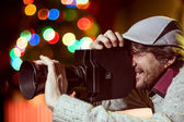 A man wearing a cap with an old movie camera — Stock Photo