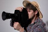 A man in a straw hat with an old movie camera on a gray backgrou — Stock Photo