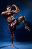 Thai boxer in full growth in a rack on a blue background — Stock Photo