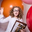 Thoughtful curly teen girl in glasses with wooden abacus on the — Stock Photo #62166687
