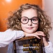 Funny, clever curly teen girl in glasses with wooden abacus on t — Stock Photo #62166845