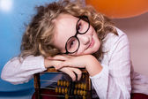 Funny, clever curly teen girl in glasses with wooden abacus on t — Stock Photo