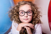 Portrait of surprised curly teen girl in glasses on the backgrou — Stock Photo
