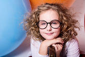 Portrait of curly teen girl with narrowed eyes on the background — Stock Photo