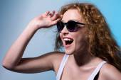 Pretty young emotional girl in sunglasses looking to the side  — Stock Photo