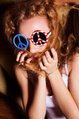 Young girl with curly hair wearing sunglasses with the American — Stock Photo
