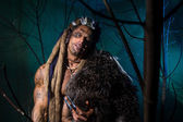 Muscular man with skin and dreadlocks among the trees — Stock Photo