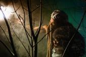 Muscular man with skin and dreadlocks looking at a bright light — Stock Photo