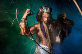 Muscular man with dreadlocks and skin through the trees. — Stock Photo