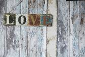 Ein Schild mit dem Wort Liebe auf dem Hintergrund der alten Wand von boa — Stockfoto